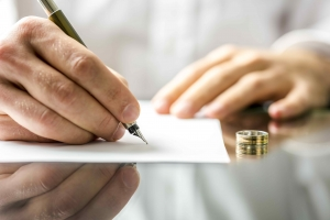 man signs his divorce documents